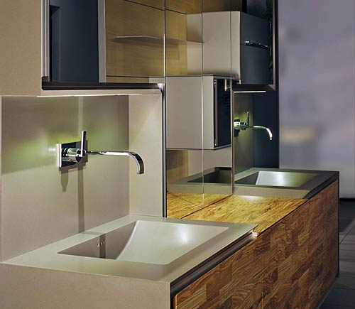 This bathroom is a design concept with olive wood; the Corian frame is wrapped-around,  mirrored overhead cabinets, LED lighting; drawer interior made in olive wood by Nagel, the premium brand